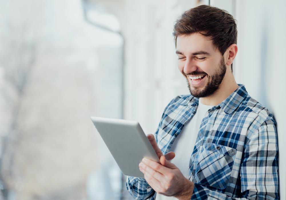 Ein Mann bedient unser Autorensystem am Tablet und freu sich über Nutzerfreundlichkeit