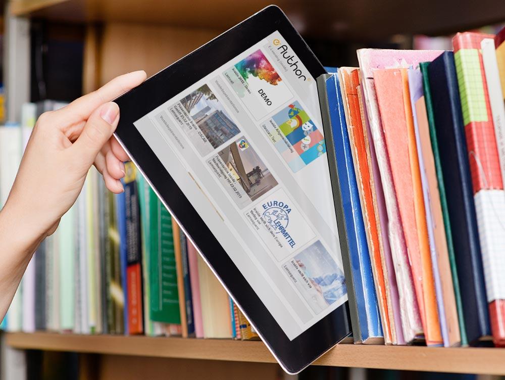 Eine Hand nimmt ein Tablet mit dem Autorensystem eAuthor auf dem Bildschirm aus einem Bücherregal
