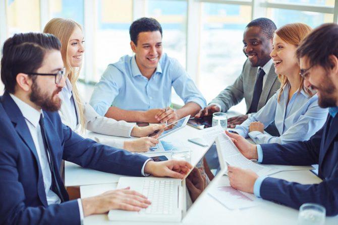 Mitarbeiter eines Unternehmens bilden sich in einer Blended Learning Maßnahme digital und analog weiter.
