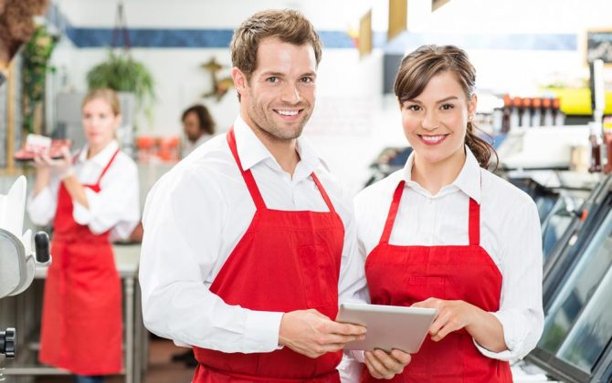 Mitarbeiter in einem Gastronomiebetrieb lernen mit der Fit in Hygiene Mitarbeiterschulung am Tablet Hygienevorschriften.