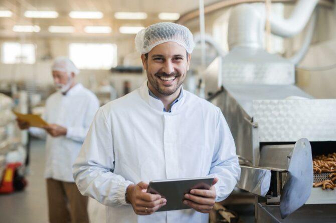 Ein Mitarbeiter in einem Lebensmittelbetrieb lernt mit Fit in Hygiene am Tablet Hygienevorschriften.