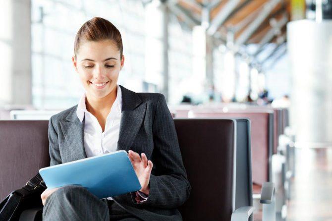 Ein Frau bildet sich auf Geschäftsreise per Mobile Learning am Tablet weiter