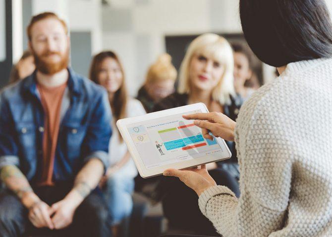 Eine Trainerin führt im Seminar mit der inside Learning- & Performance Cloud ein Fragewandspiel durch