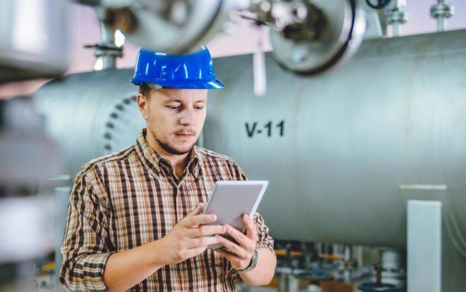 Ein Angestellter der Industrie lernt per Tablet flexibel in der Werkshalle.