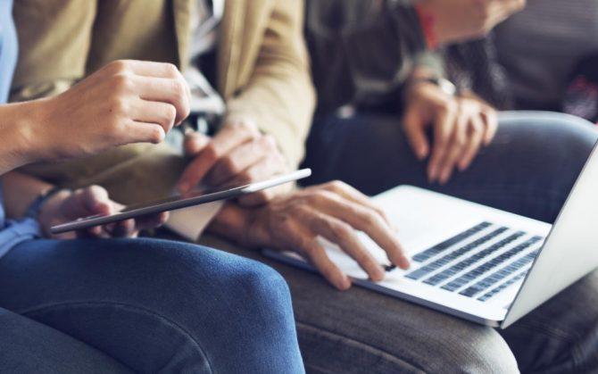Geschäftsleute lernen mit Selbstlernmedien an Laptops, Tablets und Smartphones