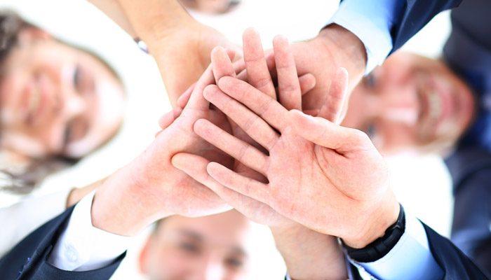 Mitarbeiter legen im Teamwork Ihre Hände zusammen