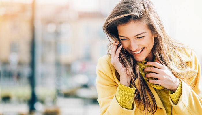 Eine junge Frau lacht zufrieden