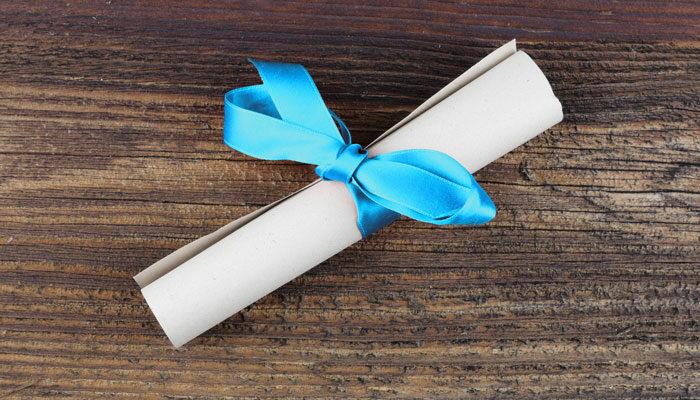 Ein zusammengerolltes Blatt Papier mit blauer Geschenkschleife