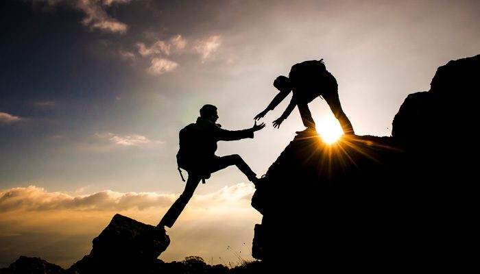 Ein hilfsbereiter Kletterer reicht einem anderen seine Hände
